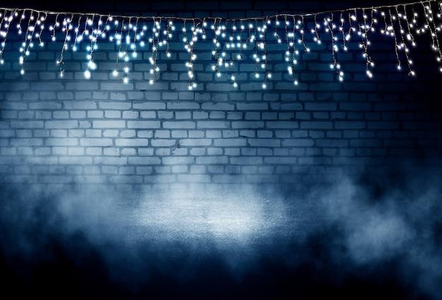 어두운 벽돌 벽에 빛 화환 아스팔트에 빛의 반사 네온 빛 연기 스모그