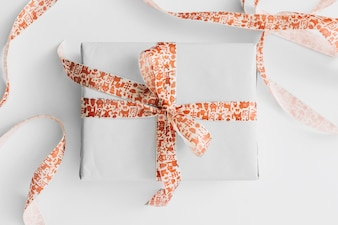 Light gift box with ribbon on white table