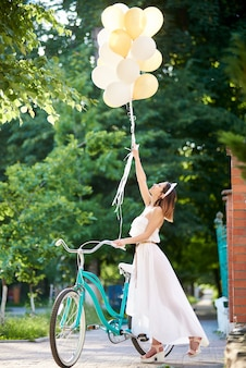 A light girl near a retro bicycle holds up the raised helium balloons in the sun's rays