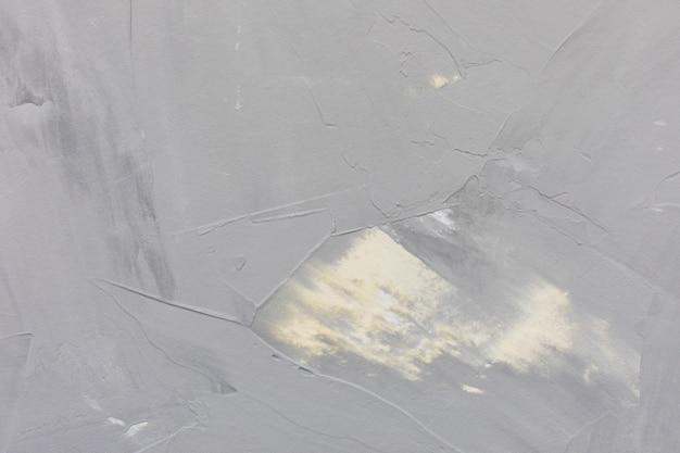 薄い灰色と黄色の粗いコンクリート壁または漆喰のテクスチャ壁