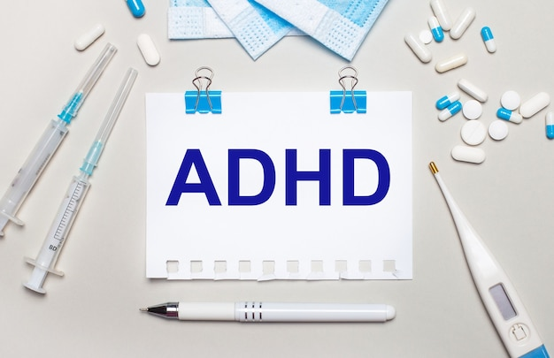 On a light gray background, blue medical masks, syringes, an electronic thermometer, pills, a pen and a notebook with the inscription adhd. medical concept