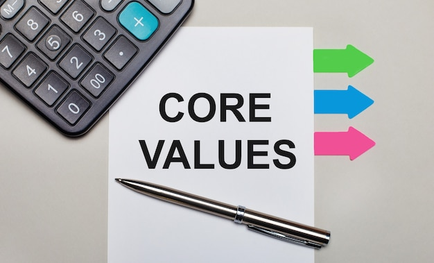 On a light gray background, a calculator, a white sheet with the text core values, a pen and bright multicolored stickers. view from above