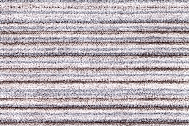 Light gray background of a knitted textile material. fabric with a striped texture closeup.