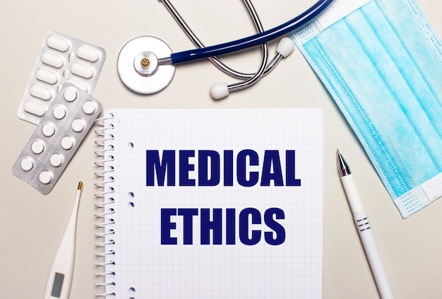 On a light gray background, a light blue disposable face mask, a stethoscope, an electronic thermometer, pills, a pen and a notebook with the inscription medical ethics. medical concept