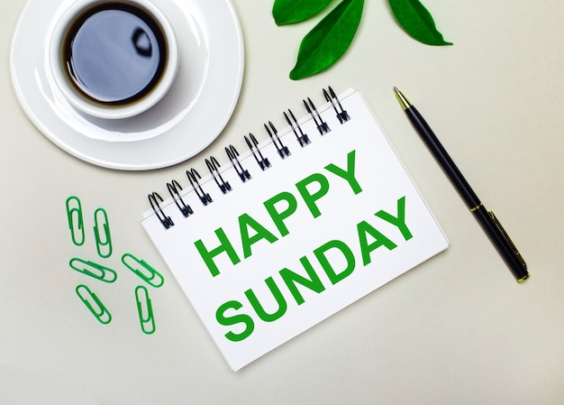 On a light gray background, a white cup of coffee, green paper clips and a green leaf of a plant, as well as a pen and a notebook with the words happy sunday.