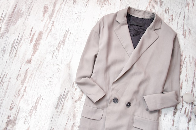 Light gray coat on a wooden background. fashion concept.