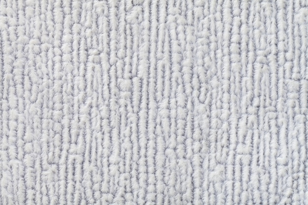Light gray fluffy background of soft, fleecy cloth  texture of textile closeup