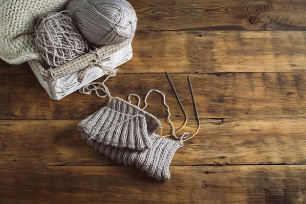 Светло-серый вяжет в корзину и спицы, белый вязаный шарф на деревянном фоне. концепция ручной работы. плоская планировка, вид сверху