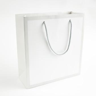 灰色の背景のデザインのライトグレーの紙袋のモックアップ。テキスト用のスペース。販売コンセプト