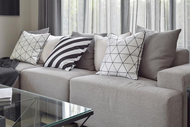 현대적인 생활 코너에서 패턴 베개가 다양한 밝은 회색 소파