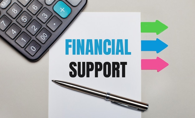 On a light gray surface, a calculator, a white sheet with the text financial support, a pen and bright multicolored stickers