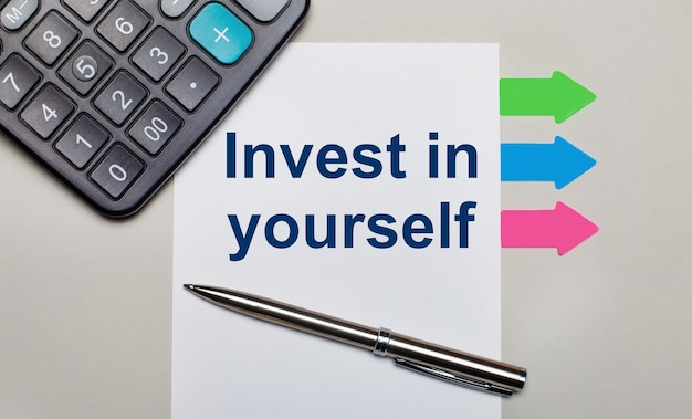 On a light gray table, a calculator, a white sheet with the text invest in yourself, a pen and bright multicolored stickers. view from above
