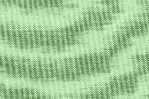 Light green background from a textile material with wicker pattern, closeup.