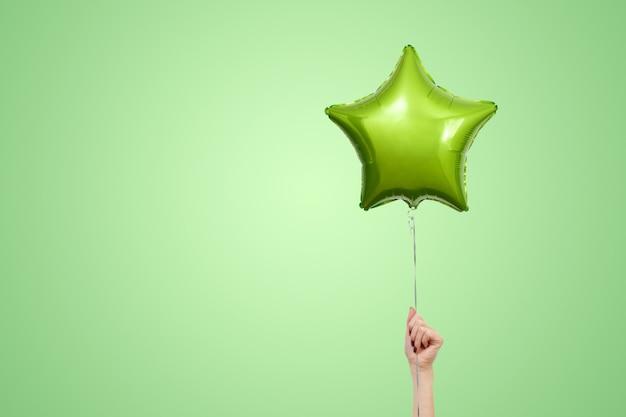 ライトグリーンの誕生日バルーンがテキストのコピースペースでクローズアップ。星型のバルーンisolatd。