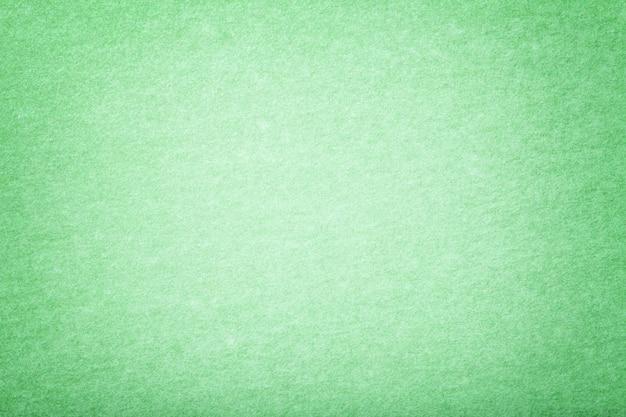 Light green matt suede fabric background. velvet texture of felt.