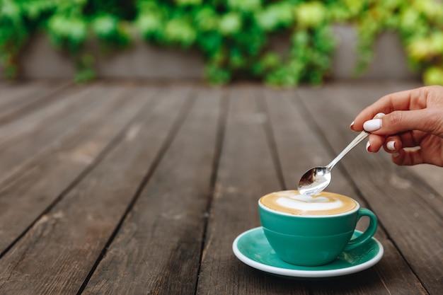 Светло-зеленая кружка свежесваренного ароматного кофе с латте-артом сверху