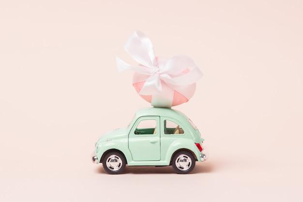 Светло-зеленый ретро игрушечный автомобиль несет пасхальное яйцо. счастливая пасхальная открытка