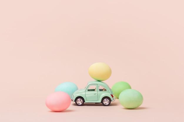 Светло-зеленый ретро игрушечный автомобиль несет пасхальное яйцо.
