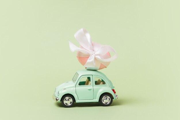 Светло-зеленый ретро игрушечный автомобиль несет пасхальное яйцо