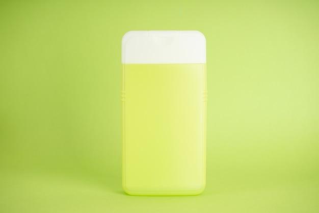 Светло-зеленая бутылка шампуня на светло-зеленом фоне, крупным планом.