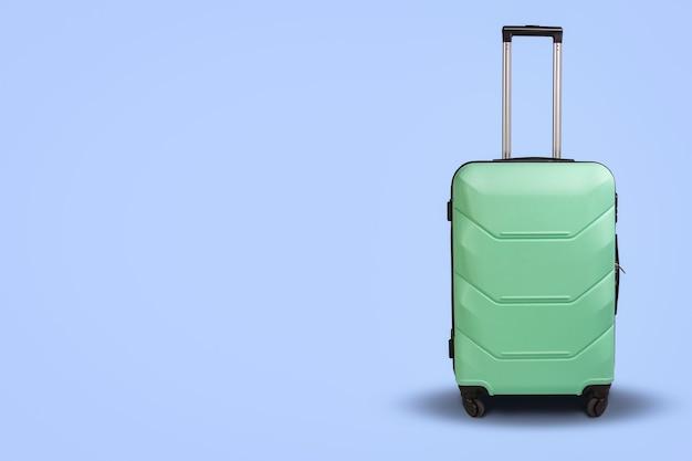 明るい青の背景に車輪の上のライトグリーンのスーツケース。旅行の概念、休暇旅行、親戚への訪問