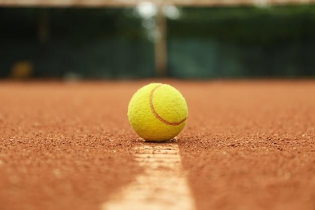 Светло-зеленый теннисный мяч на глиняном корте, крупным планом