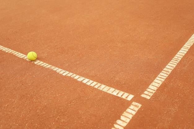 Светло-зеленый теннисный мяч на глиняном корте, место для текста