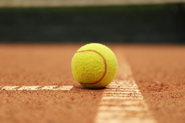 粘土のコートでライトグリーンのテニスボール