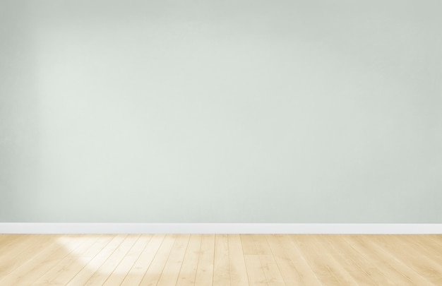 Light green wall in an empty room with a wooden floor
