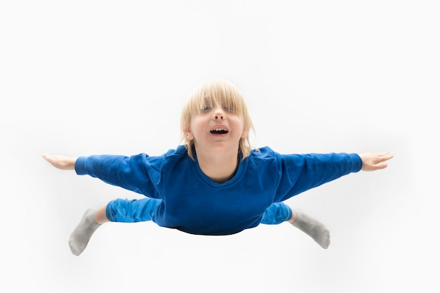 Light-haired boy in blue suit soars in the air isolated on white surface