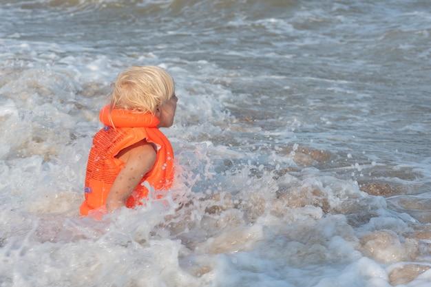 オレンジ色のインフレータブルベストを着た明るい髪の少年が海で泳いでいます。