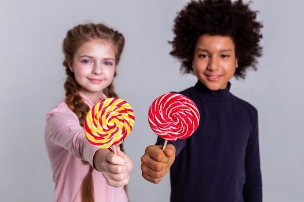 Light-haired curious girl. resolute smiling kids pulling out hands and showing multicolored candies on camera