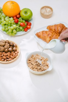 Light healthy breakfast with oatmeal. hercules, nuts, fruit, boiled eggs, bread. tableware. healthy food.