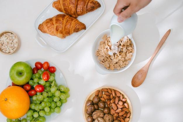 オートミールと軽い健康的な朝食。ヘラクレス、ナッツ、フルーツ、ゆで卵、パン。食器。健康食品。