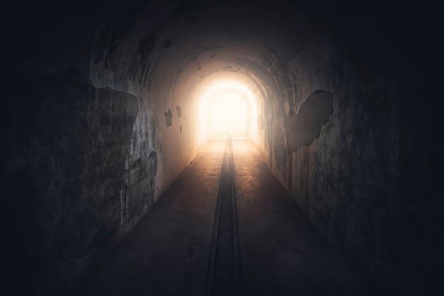 터널 끝의 빛. 버려진 벙커에 있는 긴 지하 콘크리트 복도, 톤. 지하 보호 벙커의 터널. 핵 공격에 대한 보호.