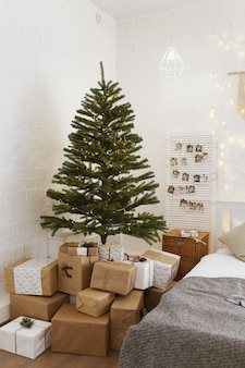 Светлый интерьер спальни украшен елкой с гирляндами и подарками
