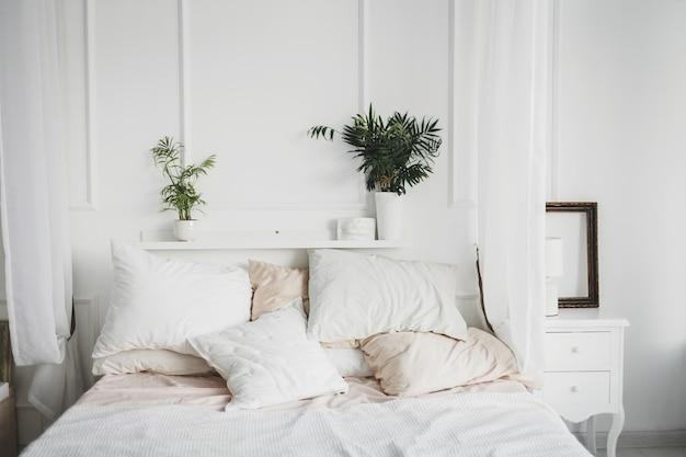 枕と植物を備えたモダンなデザインの居心地の良いベッドルームの明るいインテリア