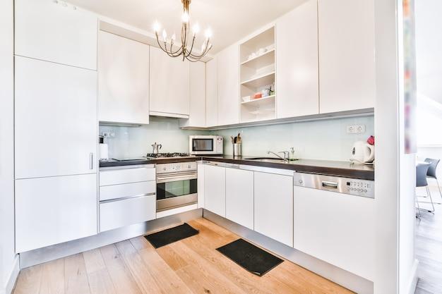 흰색 광택 캐비닛과 스테인리스 가전 제품을 갖춘 넓고 현대적인 주방의 밝은 인테리어