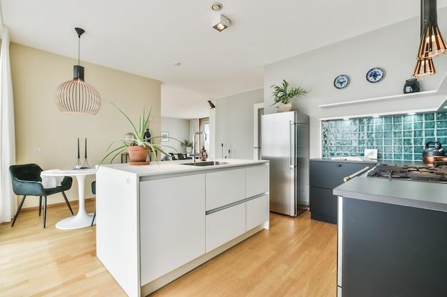 Светлая кухня с мебелью в стиле минимализма и украшениями в дневное время в современной квартире