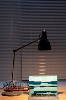 Light of lamp over laptop with blue notepapers on display and basket with highlighter near by on wooden table by window with jalousie