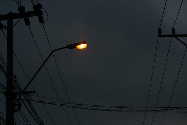 어두운 밤 하늘 배경에 전선과 기둥에 램프