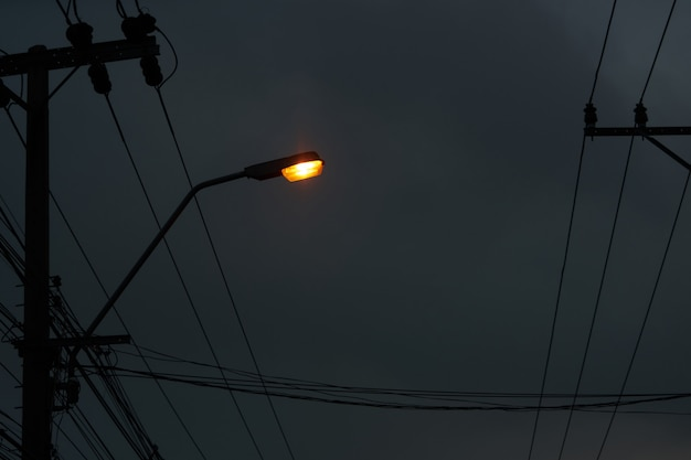 Light lamp on pole with electric wires on dark night sky background