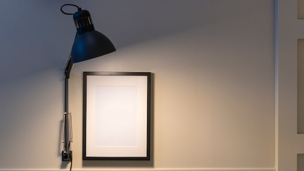 Light lamp with white frame on wall