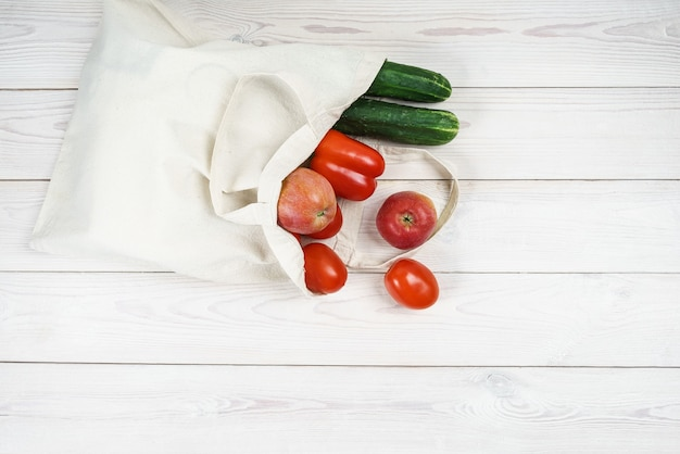 新鮮な野菜や果物が入った軽いリネンのエコバッグ。
