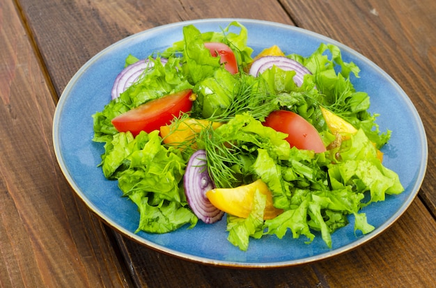 Light meal of green leaves of lettuce, yellow and red tomatoes, olive oil on wooden table.