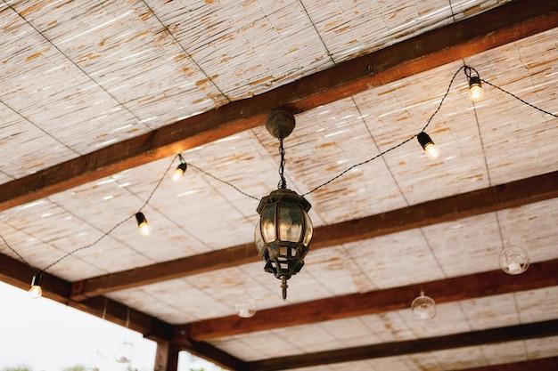 竹と花輪で作られた天井の下の軽金属シャンデリア