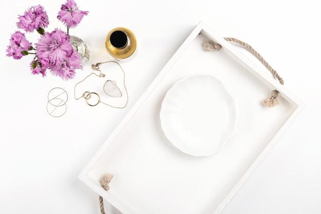 女性の香水ジュエリーと花が付いた白いテーブルでの製品プレゼンテーション用のライトモックアップ...