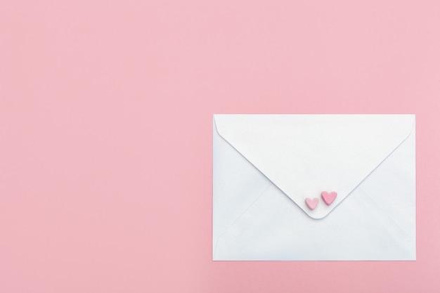 핑크에 고립 된 마시멜로에서 두 개의 하트와 가벼운 자개 종이 공예 봉투