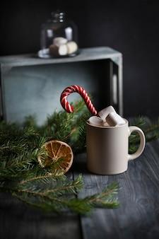 Легкая кружка с какао, украшенная зефиром и карамельными тростниками, в окружении еловых веток и сушеной дольки апельсина на деревянном фоне.