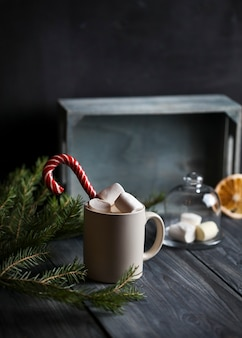 Light mug with cocoa decorated with marshmallows and caramel canes, surrounded by fir branches and a dried orange slice on a wooden background.